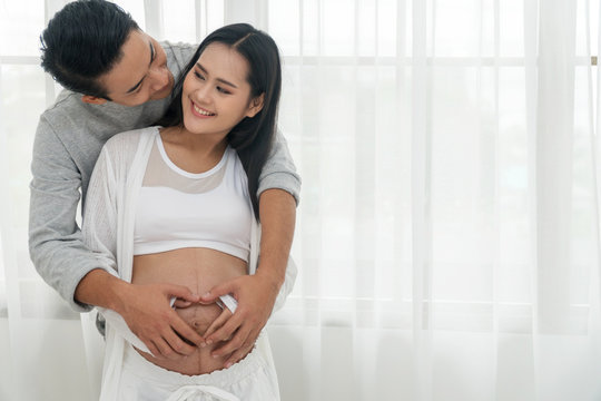 Husband embracing his wife making heart shape on the pregnant belly with their hands. Happy couple of young man hugs his pregnant beautiful wife, smiling and looking into each other's eyes at home.