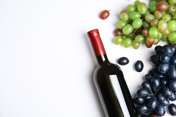 Fresh ripe juicy grapes, bottle of red wine and space for text on white background, top view