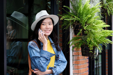 Young asian woman talking phone standing in front of cafe in the city outdoors background, people working outdoors with technology, lifestyle
