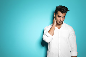 Young man with trendy hairstyle posing on color background Wall mural