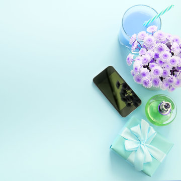 Surrealiam Composition flat lay gift to a woman. Modern gadget mobile phone glass cocktail perfume bouquet of flowers Preparing for the holiday surprise gift box Top view blue background