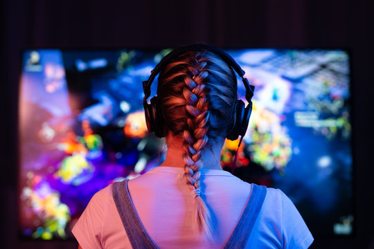 A girl is a gamer or a streamer in front of a television playing.It is possible to use as a background