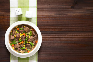 Beef stew or soup with colorful summer vegetables (pea, carrot, sweet corn, green bean, onion) in bowl, photographed overhead on dark wood with natural light