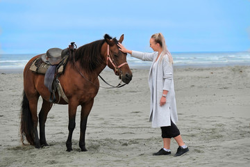 Woman patting horse on beach by the sea. Sand beach in Olympic National Park. Olympia. Washington. United States of America.