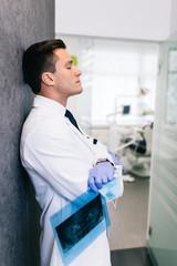 Handsome male dentist in doctors white lab coat standing in modern dental office