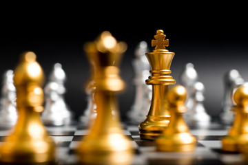 Gold king and team in chess game face with the another silver team on black background (Concept for company strategy, business victory or decision)