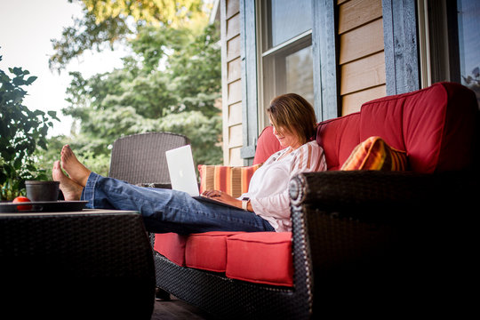 Woman sitting on front porch on soft working on laptop.