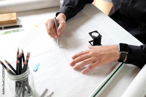 Interior designer working on the blueprints at creative