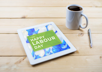 Happy Labour Day text on tablet on wooden work table with coffee mug