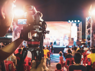 Professional digital camera recording video in music concert festival