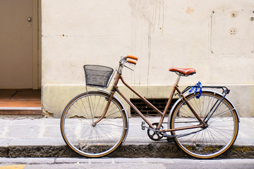 Old retro bicycle standing on a street in Florence, Italy by a wall