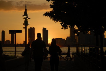 Sunset over a cityscape on the water; people walking
