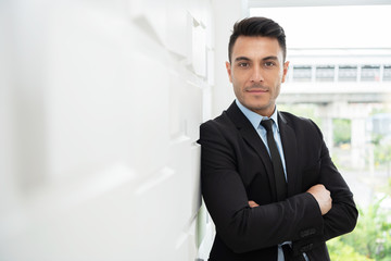 Successful Businessman standing over white wall.