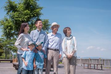 公園で空を見上げて微笑む三世代家族
