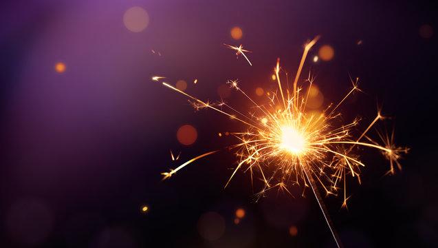 Glittering burning sparkler on purple background
