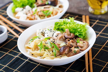 Vegan noodle soup with tofu cheese, shiitake mushrooms and lettuce in white bowl. Asian food.