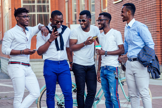 fashionable friends at a meeting. a group of five handsome African American men well-dressed businessmen having fun and communicating in the summer in the park
