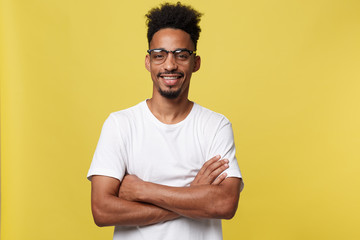 Close up portrait of a happy african american man posing with arms crossed on isolated yellow background