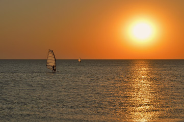 the silhouette of a windsurfer on a board under a sail moves along a calm water surface at sunset over the sea, horizon