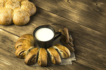 Food. Baking of confectionery. Fresh baked bakery roll with poppy seeds and sesame seeds with a cup of milk for breakfast on the background of the texture of a wooden table