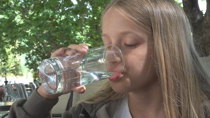Child Drinking Water at Restaurant, Kid Holding a Glass of Water, Girl Smiling