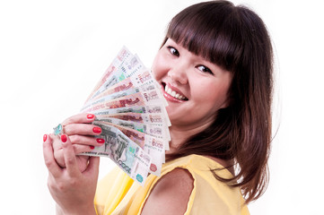 Happy brunette girl in yellow dress holding money