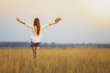 The beautiful woman standing upright, holding her hands up over her head while in the meadow, in warm sunshine. Happy relaxed girl with long hair standing in the meadow. Freedom concept