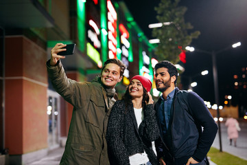 People Taking Photos On Phone On Street In Evening
