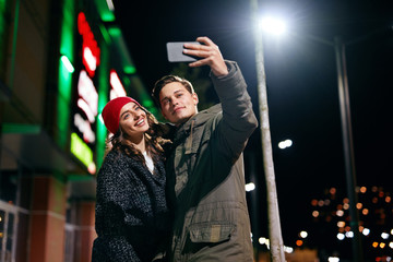 Couple Taking Photos On Phone On Street In Evening
