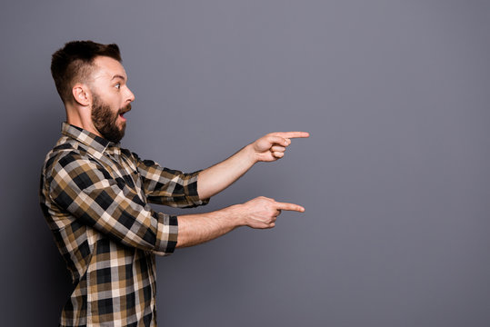 Side view photo of surprised handsome guy shows with his fingers