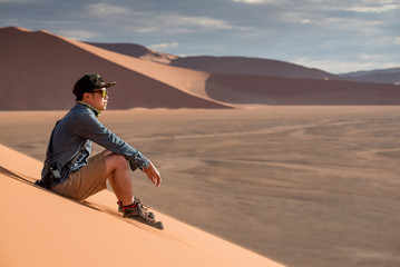 Young Asian man traveler and photographer looking at scenery while sitting on sand dune in Namib desert of Namibia, Africa. Travel photography concept
