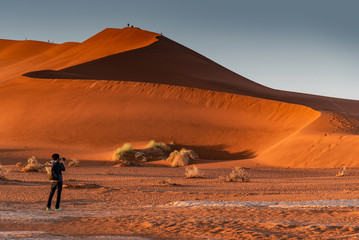 Young male traveler and photographer taking photo of sand dune during the sunrise in Namib desert, Namibia, Africa. Travel photography concept