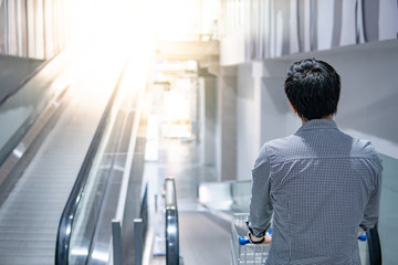 Young Asian man shopper holding shopping cart (trolley) on travelator (escalator) in supermarket or grocery store. Shopping lifestyle concept