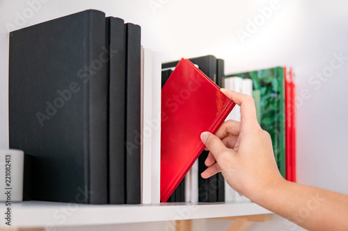 Male Hand Choosing And Picking Red Book On White Bookshelf In Public Library Education Research