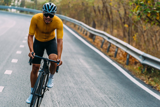 Focus on Asian man wearing a yellow cycling jersey, who's riding a road bike up high on hill in the morning. Under morning sunshine with determination on his face.