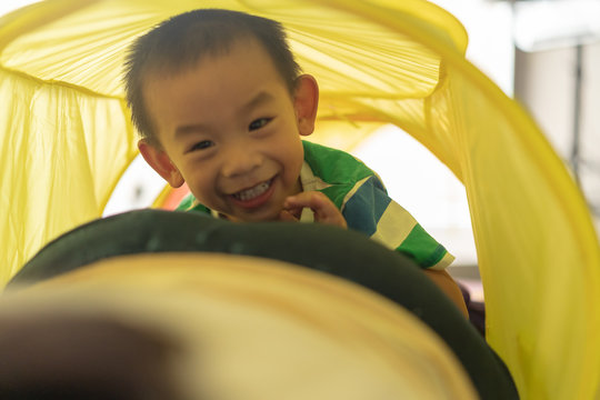 Asian boy have smile and laughing on his face while he creep through a bright colorful play tunnel, concept for learning by doing, brain develop and kid's motor skill.