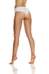 back view of female legs with white panties on white background