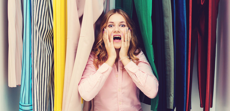 Woman choosing her fashion outfit. Sale, gifts, holidays and people concept. Girl thinking what to wear in front of many choices of clothes in organized wardrobe. Home closet or store clothing rack.