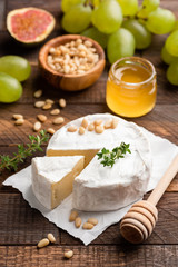 Brie or camembert with pine nuts, figs, honey and green grapes on brown wooden serving board. Closeup view, selective focus