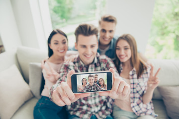 All attention to the smartphone Focus on screen of modern phone with a blurry background with four young people take selfie sitting on a sofa in denim clothes