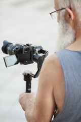Portrait of aged photographer holding camera and going to make photo