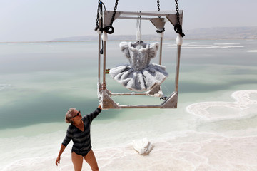 Israeli artist Sigalit Landau holds onto a metal frame containing her artwork, a ballerina's tutu covered in salt crystal formations, as it is removed from the hyper-saline waters of the southern Dead Sea, Israel
