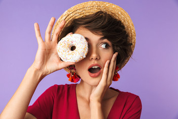Photo of positive woman 20s in straw hat holding sweet donut, isolated over violet background