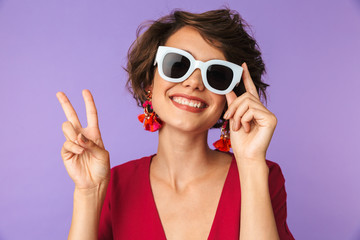 Image of fashionable brunette woman 20s in straw hat and sunglasses showing peace sign, isolated over violet background