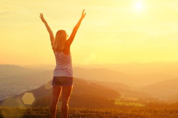 Happy woman with open arms stay on the peak of the mountain clif