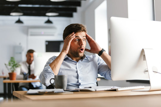 Shocked confused male manager using compuer and holding head