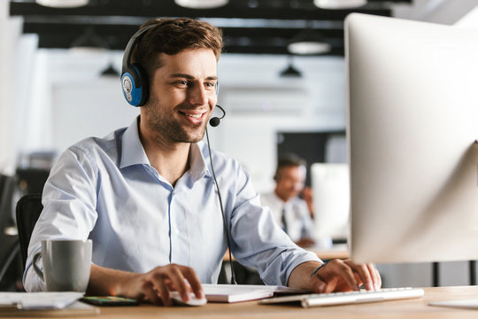 Photo of young worker man 20s wearing office clothes and headset, smiling and talking with clients in call center