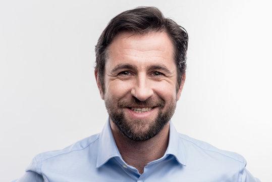 Mature man. Good-looking mature man wearing blue shirt smiling broadly on image without face retouching