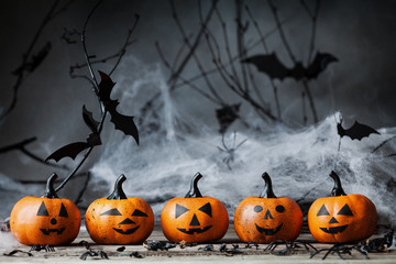 Halloween pumpkin heads with funny smile and spooky decoration on dark wood.