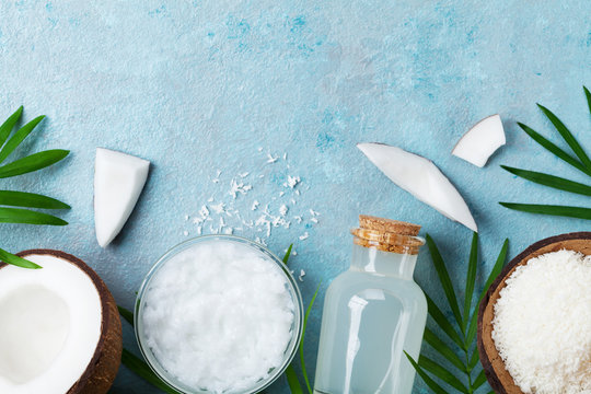 Natural coconut products for spa, cosmetic or food ingredients. Oil, water and shavings on blue table top view. Flat lay.